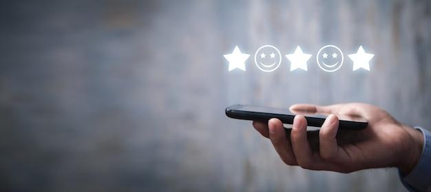 Homem segurando smartphone com um rosto sorridente e estrelas. comentários. satisfação do cliente