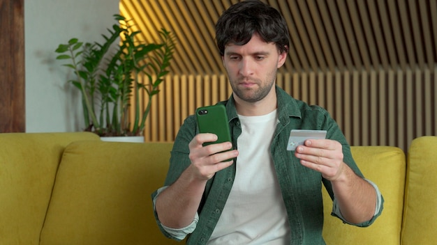 Homem segurando smartphone e cartão de crédito, compras on-line, compra na loja de internet, sentado no sofá amarelo em casa.