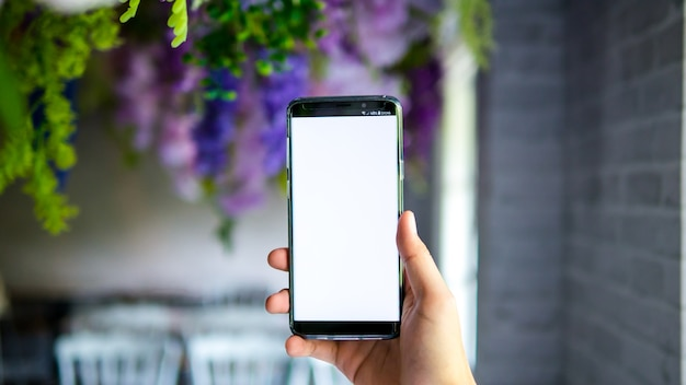 Homem, segurando, smartphone, exposição, tela branca, para, mockup, app, ligado, borrão, fundo, em, decoratio