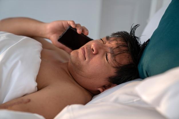 Homem segurando smartphone recebe uma ligação durante o sono em uma cama branca pela manhã com o rosto sonolento