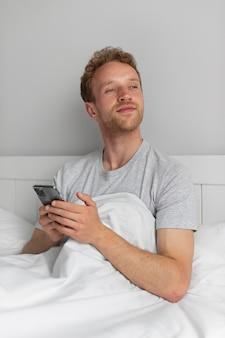 Homem segurando smartphone, tiro médio