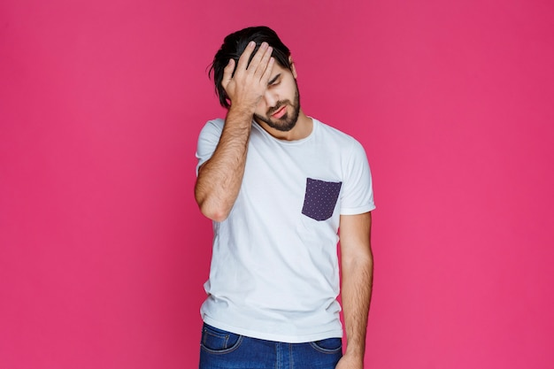 Homem segurando sua cabeça como se tivesse dor de cabeça ou um grande problema.
