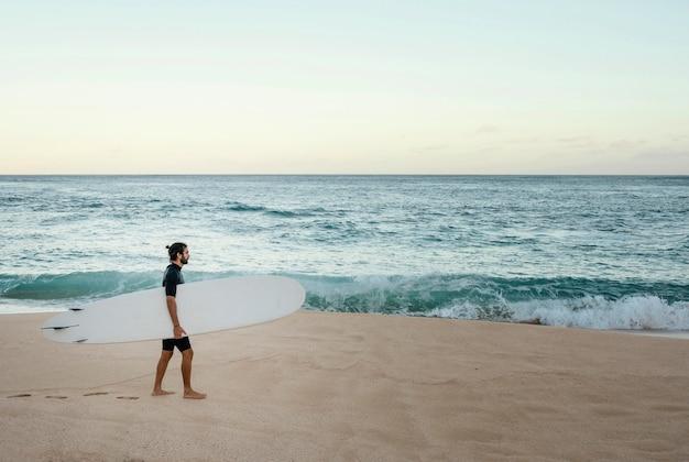 Homem segurando sua prancha de surfe próximo ao oceano