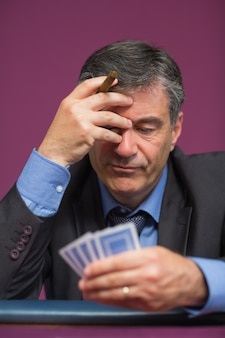 Homem segurando suas cartas pensando