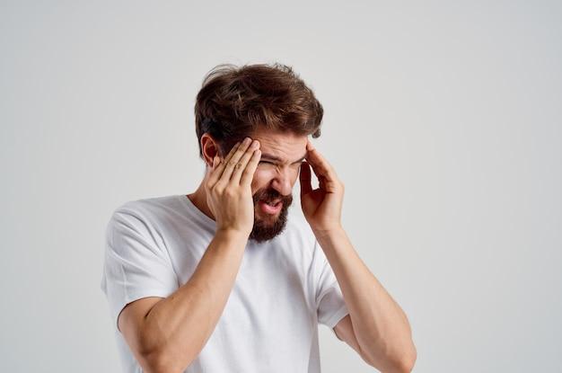 Homem segurando suas emoções de estresse de dor de cabeça fundo isolado