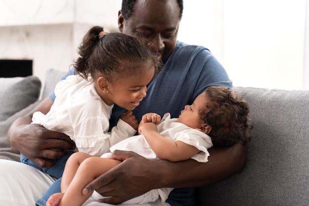 Homem segurando suas filhas nos braços