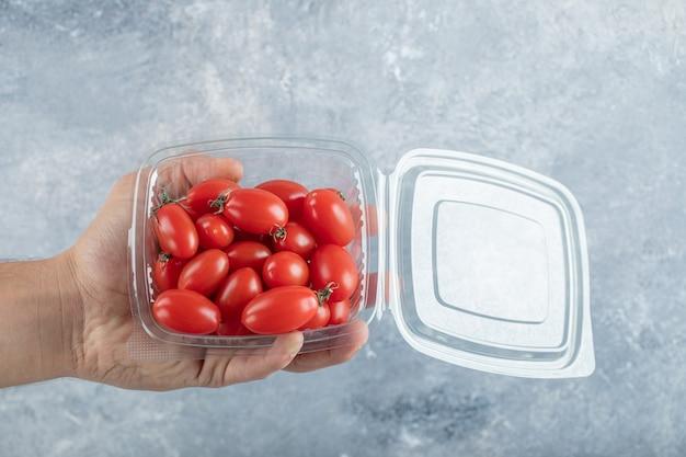 Homem segurando suculentos pequenos tomates-cereja vermelhos e laranja. foto de alta qualidade