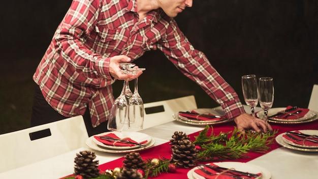 Homem, segurando, taças champanha, enquanto, decorando tabela