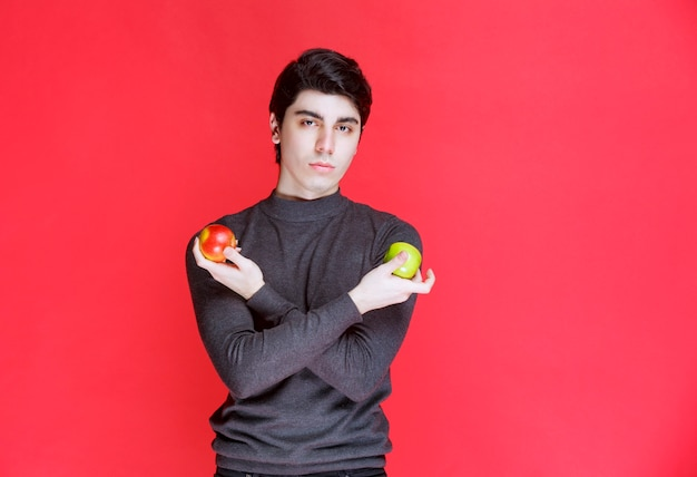 Homem segurando tangerina verde e maçã vermelha na mão