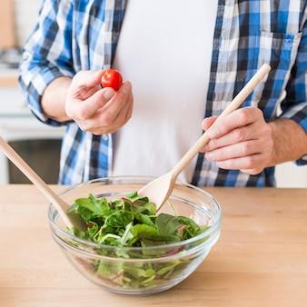 Homem, segurando, tomate cereja, em, mão, preparar, a, fresco, salada verde, em, a, tigela, ligado, madeira, superfície