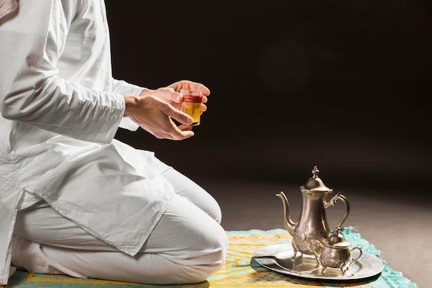 Homem segurando tradicional chá árabe em um copo