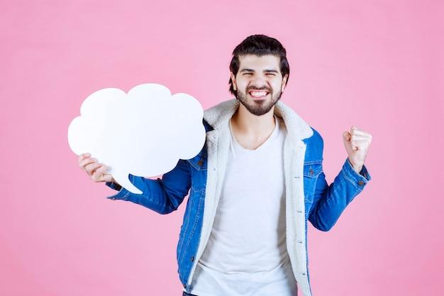 Homem segurando um balão de fala em branco de forma de nuvem e se sentindo um vencedor.