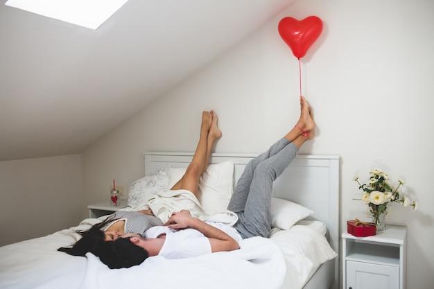 Homem segurando um balão em forma de coração com os pés