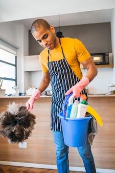 Homem segurando um balde com produtos de limpeza