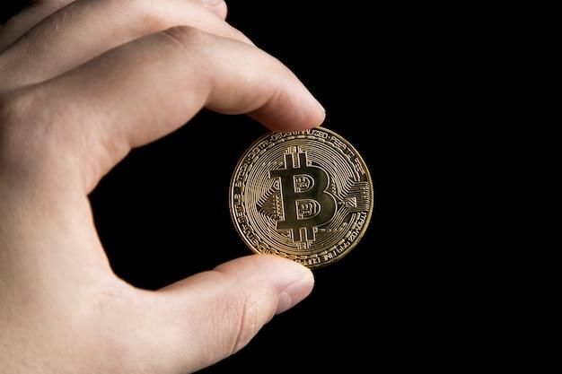 Homem segurando um bitcoin de ouro
