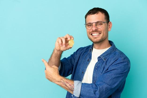 Homem segurando um bitcoin