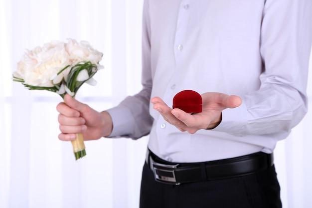 Homem segurando um buquê de casamento e um anel na superfície clara