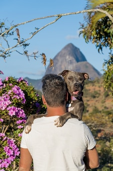 Homem segurando um cachorro pit bull nos braços e admirando a natureza e as montanhas de petrópolis, rio de janeiro, brasil. relação afetuosa entre humano e animal.