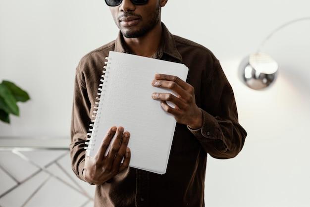 Homem segurando um caderno braille