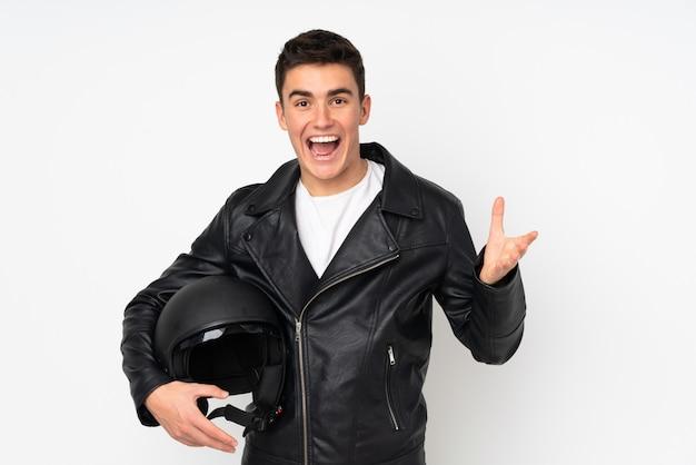 Homem segurando um capacete de moto isolado no branco infeliz e frustrado com algo