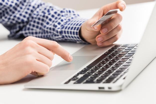 Homem segurando um cartão de crédito e digitando. compras on-line na internet usando um laptop