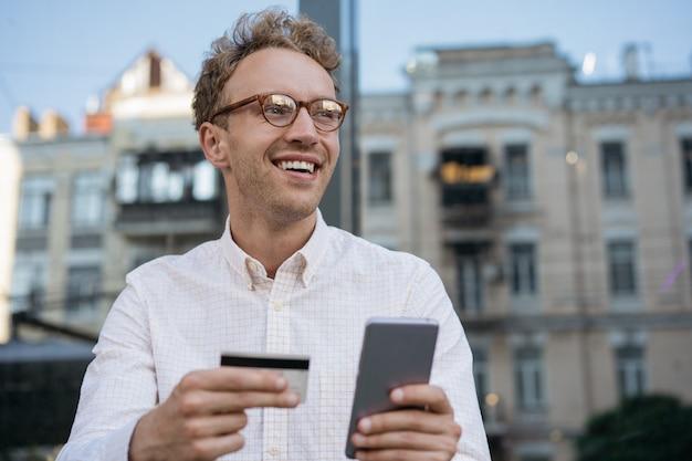 Homem segurando um cartão de crédito usando o aplicativo móvel para compras online freelancer sorridente verifica o saldo do cartão