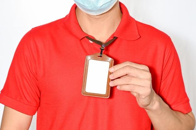 Homem segurando um cartão de identificação de funcionário vazio, branco em branco, para maquete de cartão de identificação