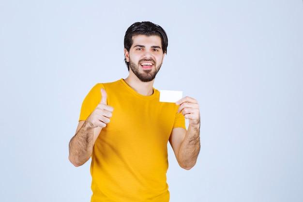 Homem segurando um cartão de visita e aparecendo o polegar.