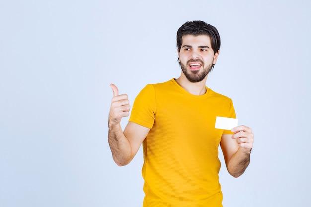 Homem segurando um cartão de visita e apontando para seu parceiro.