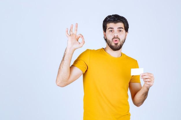 Homem segurando um cartão de visita e mostrando um gesto de ok