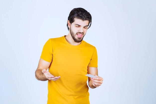 Homem segurando um cartão de visita e verificando os detalhes do contato.