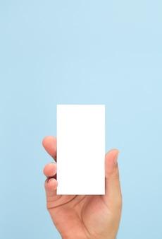 Homem segurando um cartão de visita em branco sobre fundo azul claro