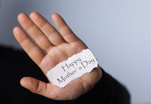 Homem segurando um cartão parabenizando as mulheres no dia das mães
