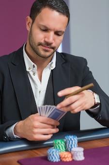 Homem segurando um charuto olhando seus cartões