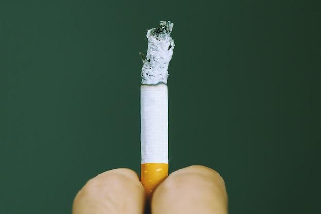Homem segurando um cigarro na mão. a fumaça do cigarro se espalhou.