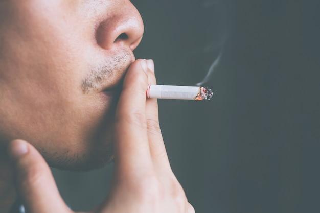 Homem segurando um cigarro na mão.