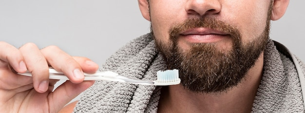 Homem segurando um close-up de escova de dentes