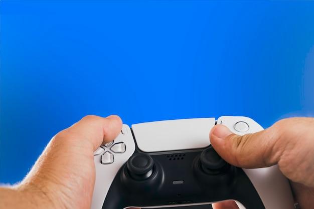 Homem segurando um controlador de jogo branco de próxima geração isolado em fundo azul. chave de croma.