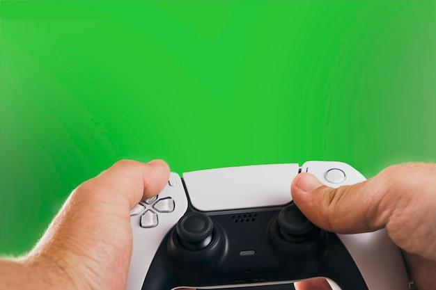 Homem segurando um controlador de jogo branco de próxima geração isolado em fundo verde. chave de croma.