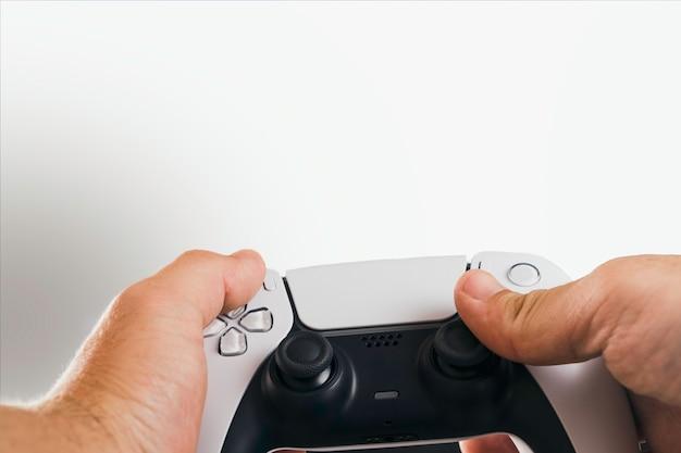 Homem segurando um controlador de jogo branco de próxima geração isolado no fundo branco.