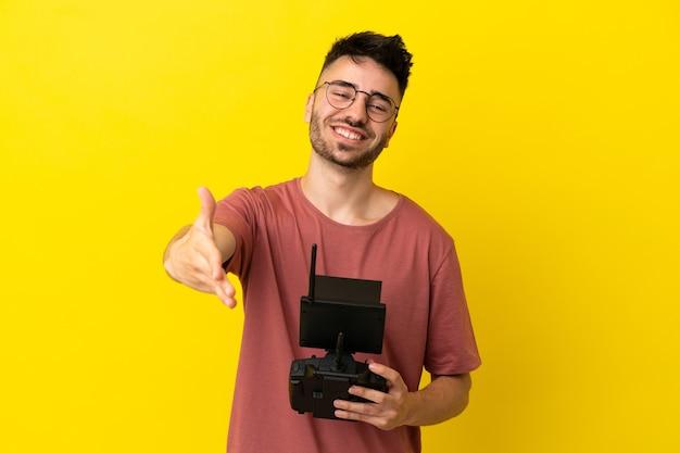 Homem segurando um controle remoto de drone isolado em um fundo amarelo apertando as mãos para fechar um bom negócio