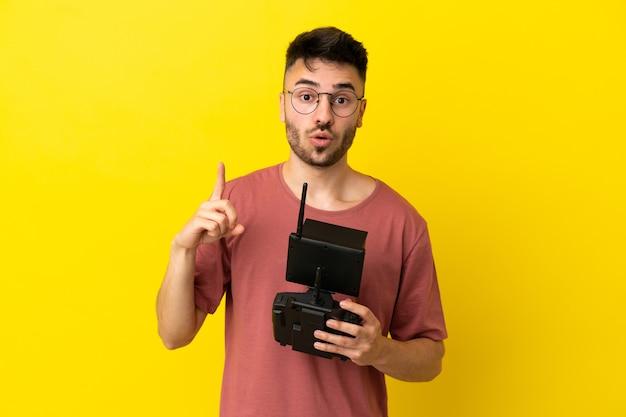 Homem segurando um controle remoto de drone isolado em um fundo amarelo com a intenção de perceber a solução enquanto levanta um dedo