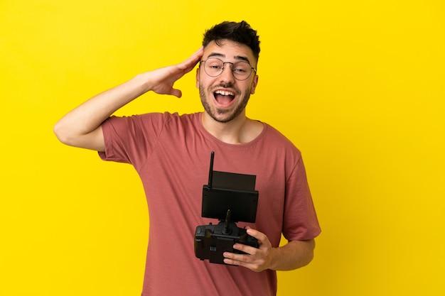 Homem segurando um controle remoto de drone isolado em um fundo amarelo com expressão de surpresa