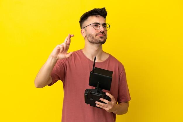 Homem segurando um controle remoto de drone isolado em um fundo amarelo com os dedos se cruzando e desejando o melhor