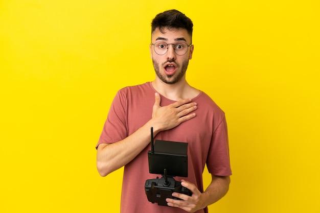 Homem segurando um controle remoto de drone isolado em um fundo amarelo surpreso e chocado ao olhar para a direita
