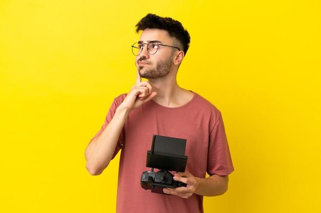Homem segurando um controle remoto de drone isolado em um fundo amarelo, tendo dúvidas e pensando