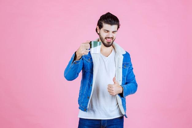Homem segurando um copo de bebida e se sentindo satisfeito