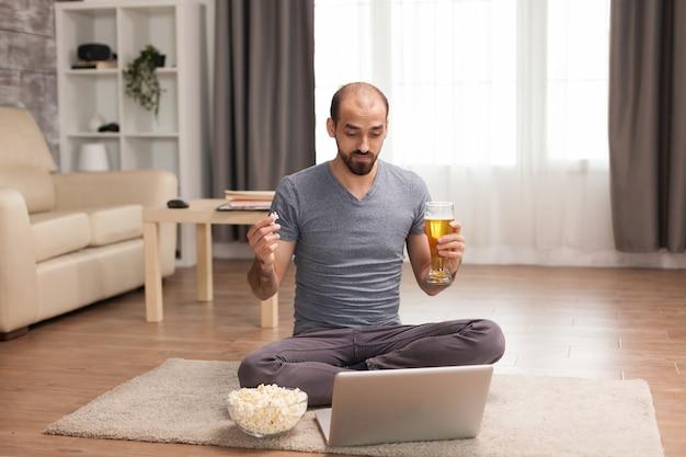 Homem segurando um copo de cerveja, conversando com amigos durante uma videochamada.