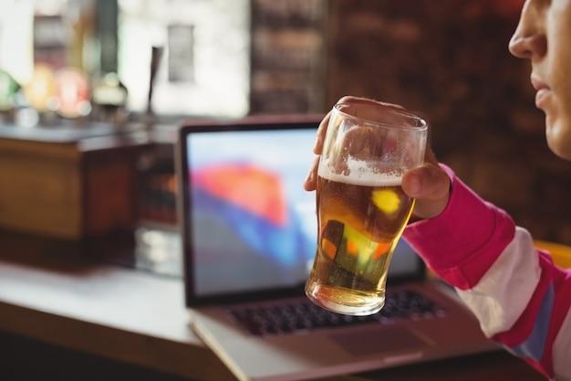 Homem segurando um copo de cerveja