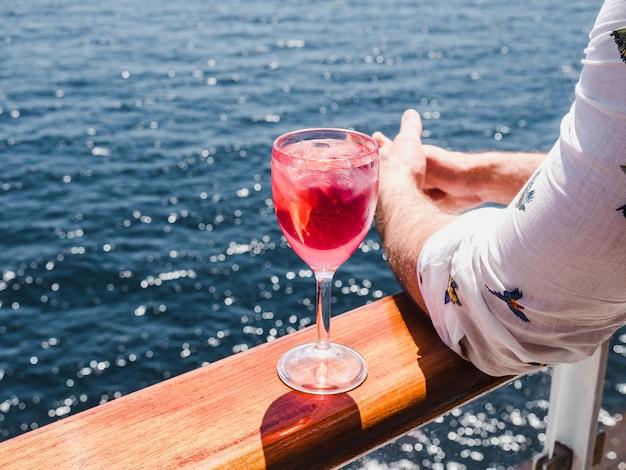 Homem segurando um copo de vinho rosa